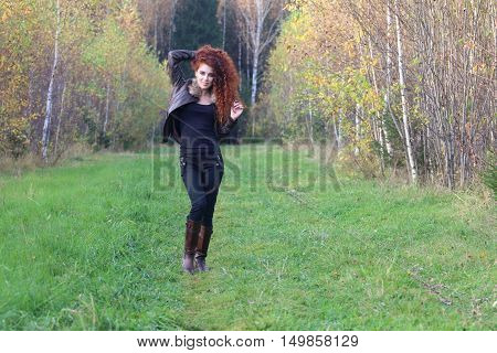 Pretty young woman in leather jacket stands on grass in autumn forest