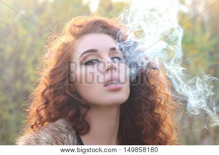 Beautiful woman with red hair in jacket with smoke in sunshine shallow dof