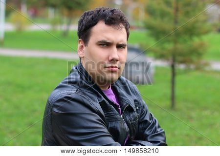 Handsome serious man in leather jacket looks at camera in park at summer