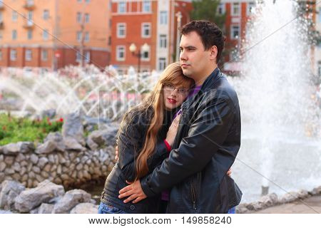 Man embraces woman in leather jacket near fountain in autumn park