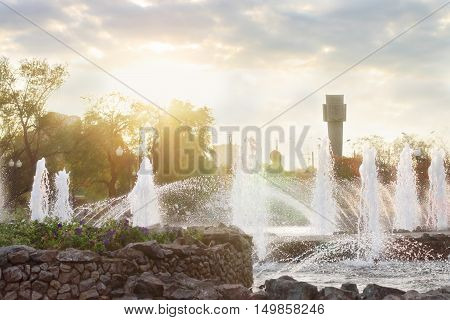 Beautiful fountain with many splashes and sun in autumn city