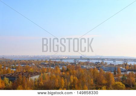 Cars trucks move on bridge ships are on water of river at autumn sunny day in city