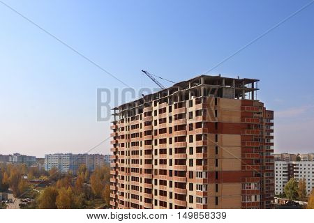 Tall brick building under construction at autumn sunny day pure blue sky