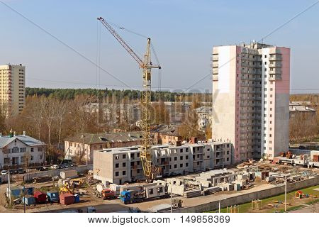 Crane trucks on construction site and new tall concrete building at autumn day