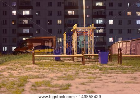 Children playground at night near buildin and cars at summer night