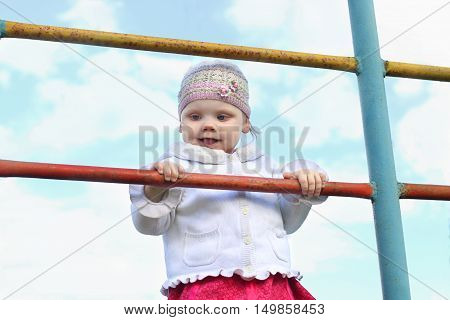 Little cute happy girl in hat climbs on ladder outdoor at summer day
