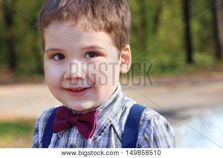 Handsome little boy in shirt and bow tie smiles in sunny green park