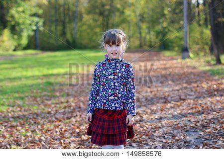 Cute little girl in red skirt stands in sunny green park with dry foliage