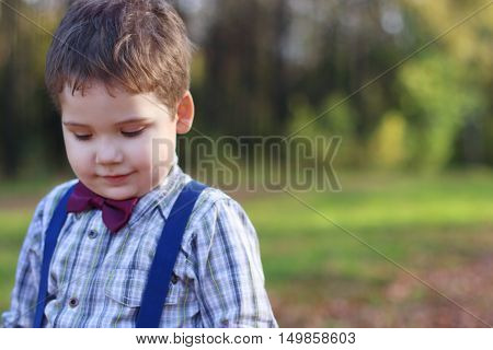 Handsome little boy with bow tie looks down in green park shallow dof