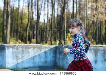 Cute little girl in red skirt runs in sunny green park with old fountain