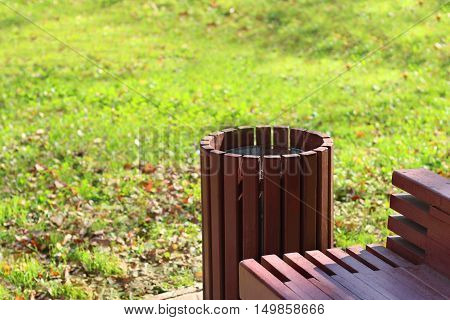 Closeup of bench and garbage can in park and green grass in blurred background