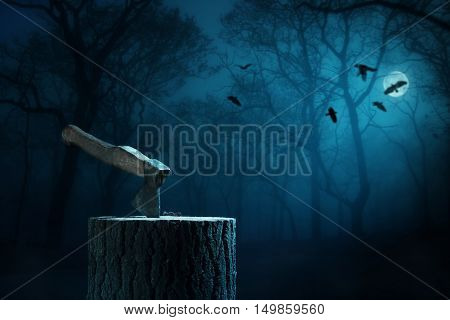 The axe stuck in the stump in a spooky night forest