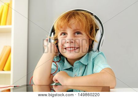 learning and next generation concept, young boy dreaming in headphones