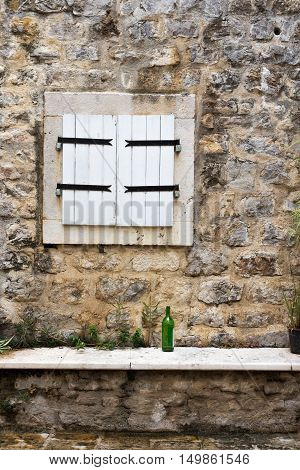 Closed White Window Shutters In A Stone Wall With A Green Wine Bottle