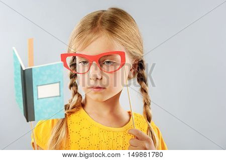 creativity and masquerade concept, little girl looking thru fake glasses