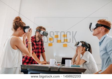Business team using virtual reality headset in office meeting. Developers meeting with virtual reality simulator around table in creative office.