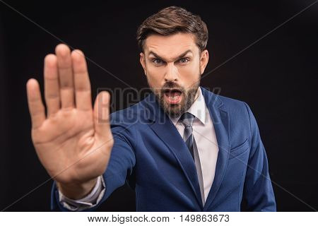 Stop. Angry male boss is stretching arm forward and shouting. Man is standing and looking at camera with irritation. Isolated