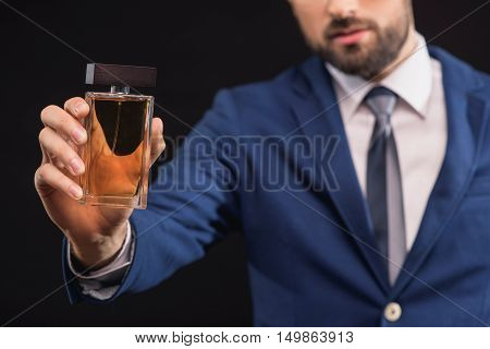 This is a real masculine cologne. Confident young man is showing scent bottle to camera. Isolated