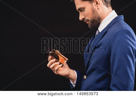 Successful businessman is standing and holding perfume. He is looking at bottle with interest. Isolated and copy space in left side