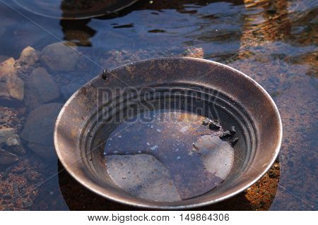 Empty gold pan for gold panning in water
