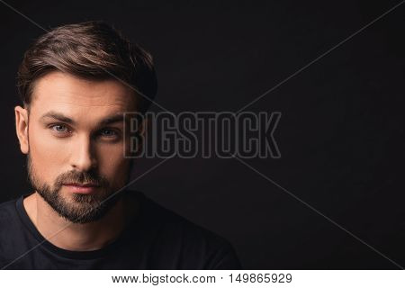 Confident young man is standing and looking forward seriously. Isolated and copy space in right side
