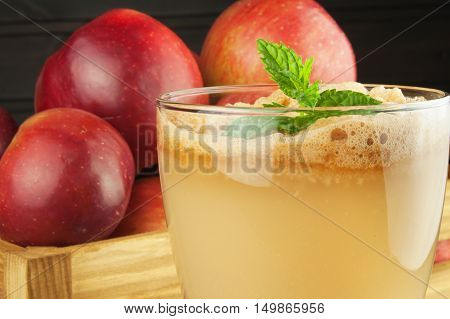 Fresh pressed apple juice unfiltered. Apple juice and apples on wooden table. A healthy juice for athletes. Autumn apple harvest.