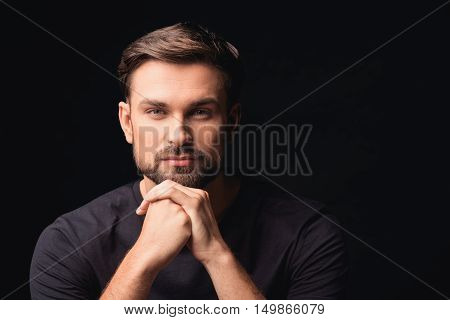 Cheerful young man is looking at camera with confidence. Isolated on black background