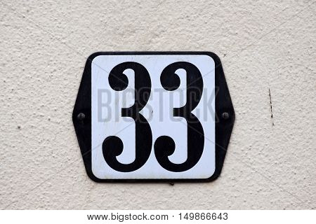 Enamelled house number thirty-three sign on a wall