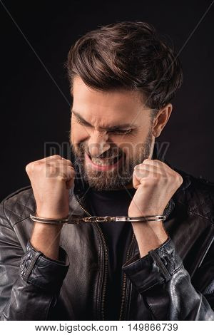 Male criminal is trying to get rid of handcuffs. He is standing and straining himself with efforts. Isolated