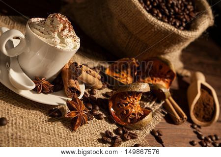 Close-up of a cup of coffee with whipped cream cocoa powder star anise cinnamon and dried orange fruit