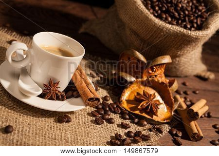 Close-up of coffee cup with star anise cinnamon and dried orange fruit