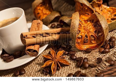 Close-up of cup of coffee with cinnamon dried orange fruit and star anise