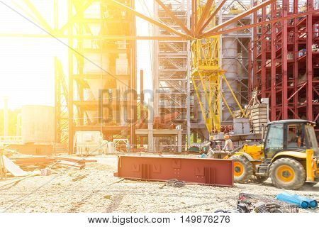 Industrial Construction. Workers Assemblers On The Excavator On The Construction Of An Industrial Facility. Tinted Image. Selective Focus