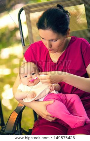 Mother feeding baby girl food to baby