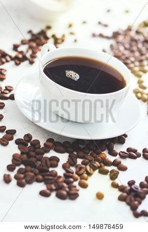 Cup of coffee with steam and coffee beans closeup selective focus