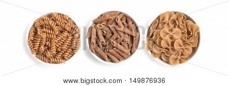 Wholemeal Pasta. Penne and Fusilli isolated in white background