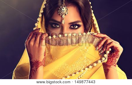 Beautiful indian girl . Young hindu woman model  with tatoo mehndi  and kundan jewelry . Traditional Indian costume yellow saree . Indian or Muslim woman covers her face.