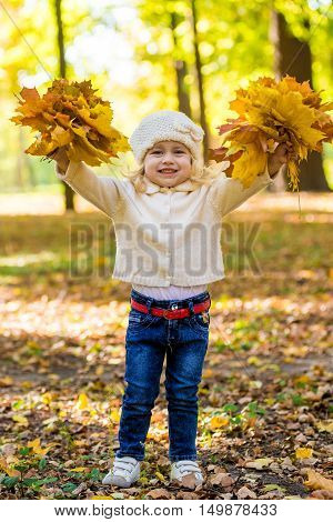 Joyful little girl in park in autumn with leaves in her hands in white knitted cap sunny day