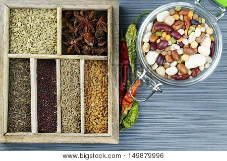 Indian spices in the spice box on a stone background with dried red chili pepers selective focus.