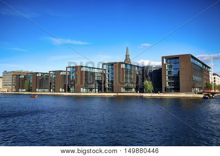 COPENHAGEN DENMARK - AUGUST 16 2016: Beautiful view on Copenhagen waterfront modern buildings and behind medieval church tower in Copenhagen Denmark on August 16 2016.