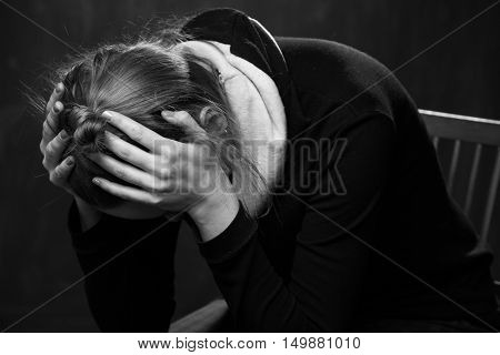 Sad woman holding the head in the hands black and white
