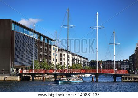 COPENHAGEN DENMARK - AUGUST 16 2016: Beautiful view on the modern Circle Bridge ( Cirkelbroen ) and canal with tourist boat in Copenhagen Denmark on August 16 2016.