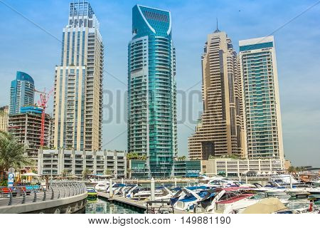 Dubai, United Arab Emirates - May 2, 2013: views of Dubai Marina skyscrapers and motorboats docked at Pier 7.