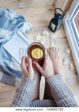 Close up view from above of woman's hands holding cup of tea with lemon. Magazine and lantern lights on wooden floor