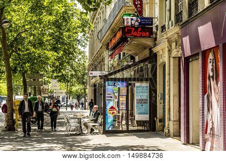 Man Sitting In A Typical Bar With Tabac Shop And Winter Gardenn At The Walk Way