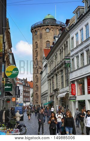 COPENHAGEN DENMARK - AUGUST 15 2016: Many pedestrians in Kobmagergade street view on Rundetaarn built by king Christian the fourth in the years 1637-42 in Copenhagen Denmark on August 15 2016.