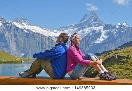 Travelers on a bench enjoying Alpine panorama. Jungfrau region, Switzerland