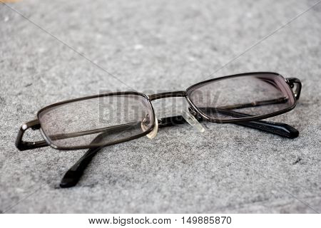 Men's glasses with a thin rim on a gray background closeup. Glassess in the folded state