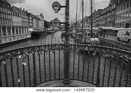 COPENHAGEN DENMARK - AUGUST 15 2016: Black and white photo boats in the docks Nyhavn people and colorful architecture. Nyhavn a 17th century harbour in Copenhagen Denmark on August 15 2016.
