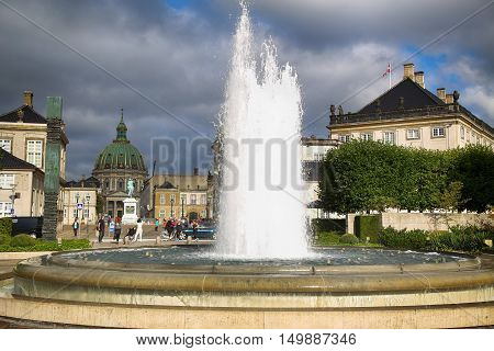 COPENHAGEN DENMARK - AUGUST 15 2016: A fountain in the Amalie Garden with many tourist in the background is Frederik's Church and Sculpture of Frederik V in Copenhagen Denmark on August 15 2016.